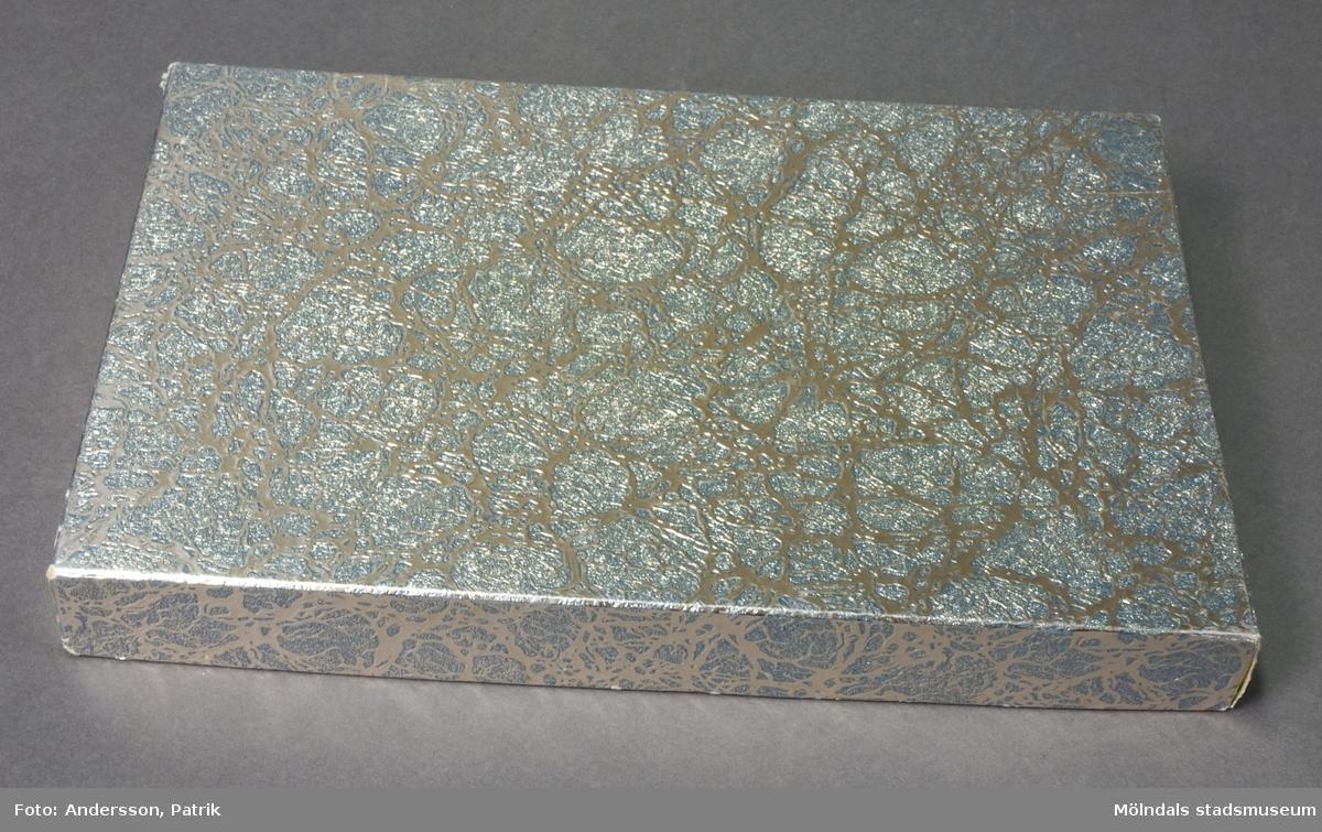 Kartong med lock. Underdel av vit papp, med siffrorna 1212/98 tryckt på undersidan. Ovandelen är klädd i silverfärgat papper, präglat i oregelbundet mönster.