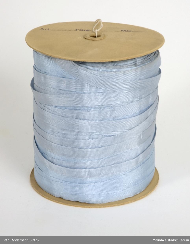 """Ljusblått sidenband på rulle, som använts vid tillverkningen av produkter på Kuverteringen, Papyrus. Bandet är lindat på en papprulle med rund platta i var ända. Ena sidan är märkt med blyerts """"Ti (texten är något otydlig) 1242/24, blå cp., 500"""". """"Blå"""", avser färgen på bandet och """"500"""" är bandets längd på rullen i meter."""