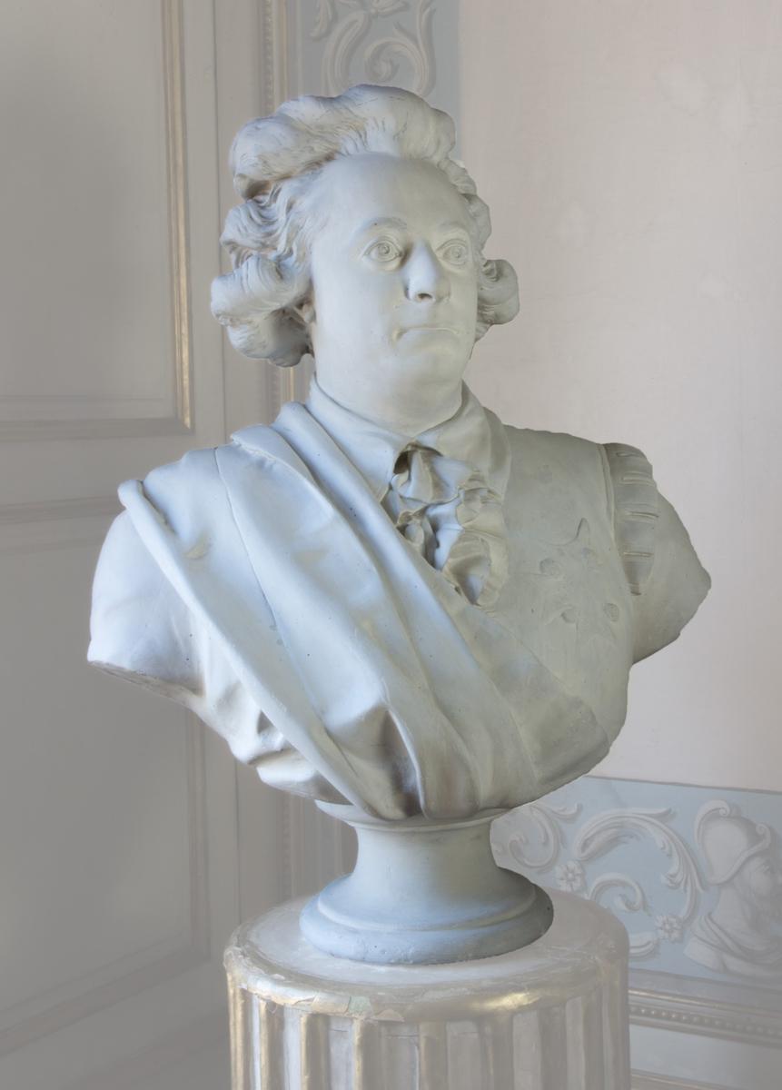 Byst av obehandlad gips, föreställande Gustav III i Svenska dräkten med band och kraschan, troligtvis tillhörande Serafimerorden, på pelarfot.