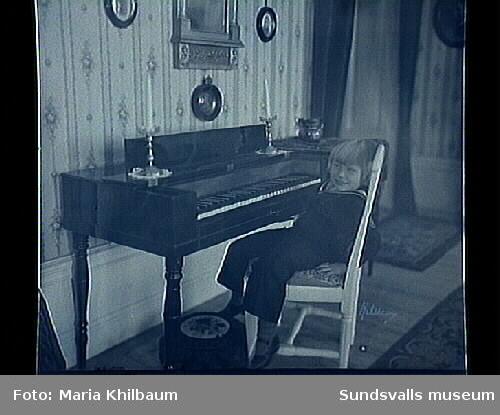 Rumsinteriör. Barn sitter vid ett piano. Hagelby