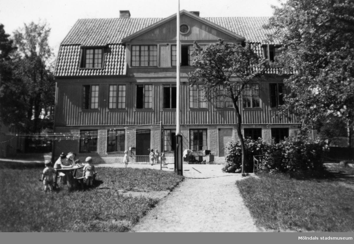 """Mölndals barnhem,  (f.d. Holtermanska) Rudbergsgatan. Framför huset står barnvagnar, barn leker i trädgården. Direktören Martin Holterman i Ostindiska kompaniet ägde Åby gård. 1782 skänkte han 3000 daler silvermynt till Fässbergs församling + ett nybyggt skolhus och trädgård på gårdens ägor vid Åby by. I skolan skulle 10 fattiga barn undervisas i """"kristendom, skrivande och något räknande. Holtermans skola fanns kvar till 1875. Då hade donationens ändamål ändrats, och man byggde i stället ett barnhem kombinerat med småskola. 1914 brann barnhemmet och 1915 byggdes ett nytt barnhem på samma tomt. 1929 överlämnades barnhemmet till Mölndals stad."""