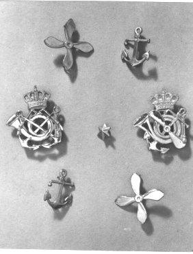 Postemblem och distinktionstecken för postpersonal på danska färjor. Antal: 6 st. Varav två propellrar, två ankare samt två krönta postemblem med ankare och propeller.
