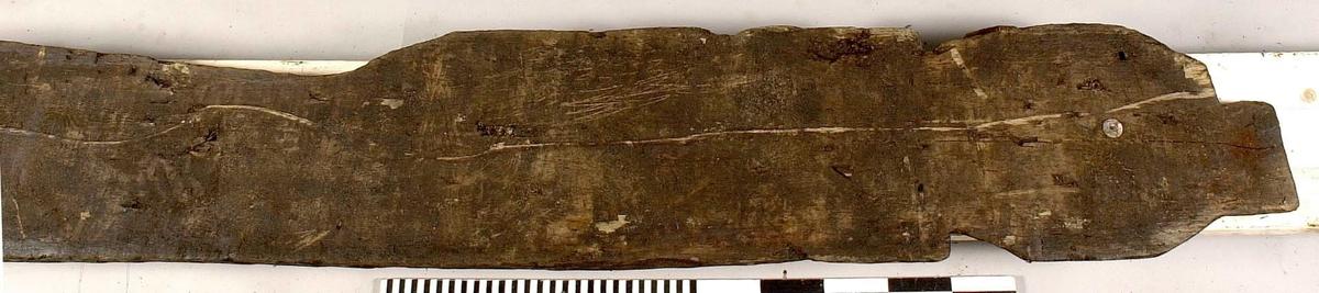 Planka. Ena änden har inhak på båda sidorna och ett rundat huvud med utskjutande topp. Andra änden är fasad och delvis snedsågad. Plankan är avsmalnande genom ett urtag på ena långsidan. 7 genomgående hål.