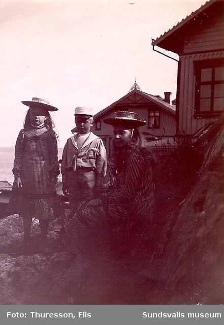 Två flickor och en pojke med bostadshus i bakgrunden.