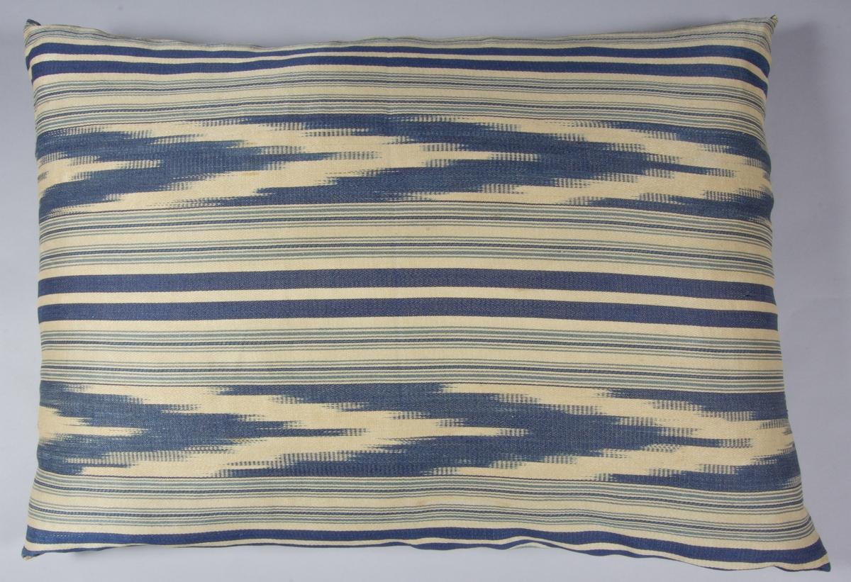 """Kudde, tillverkad med framsida av handvävt tyg, lin, satinvävt, med vit linvarp och inslag i vitt, ljusblått och mörkblått lingarn, trådränder med klarblått. Kudden är mönstrad både med """"vanliga"""" ränder och med flamgarnsränder. Baksida av vitt kypertvävt linnetyg. Kudden är sydd så att framsidan råder över baksidan. Fyllning: fjäder."""