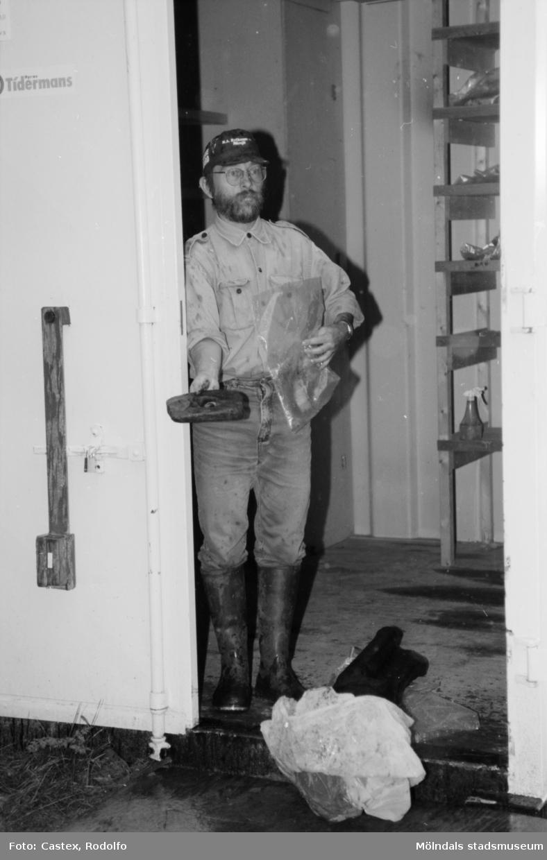 En man håller ett föremål och en plastpåse. Arkeologisk utgrävning i Tulebo mosse, augusti 1993.