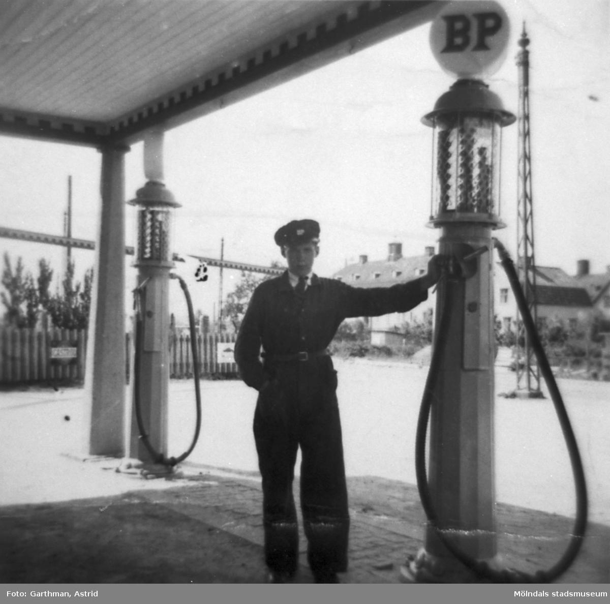 På Göteborgsvägen i Lackarebäck, snett emot lasarettet, låg denna BP bensinstation. Ville Nilsson står lutad mot en bensinpump. Kompisen Bror Eriksson jobbade också där. 1930-tal.