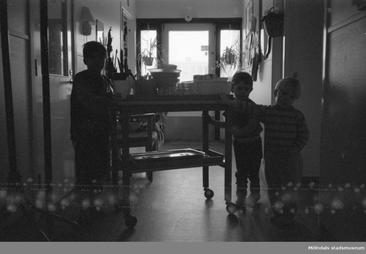 Interiör från Katrinebergs daghem. Man ser tre barn som står vid en matvagn. 1992-93.