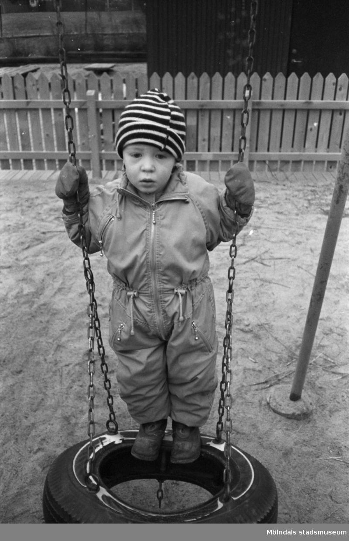 Lille Fred, ca två år, står på en gunga gjord av däck. Han har overall, mössa och vantar på sig. Marken är sandig och omgärdad av staket. Lunkentussen, Katrinebergs daghem 1992.