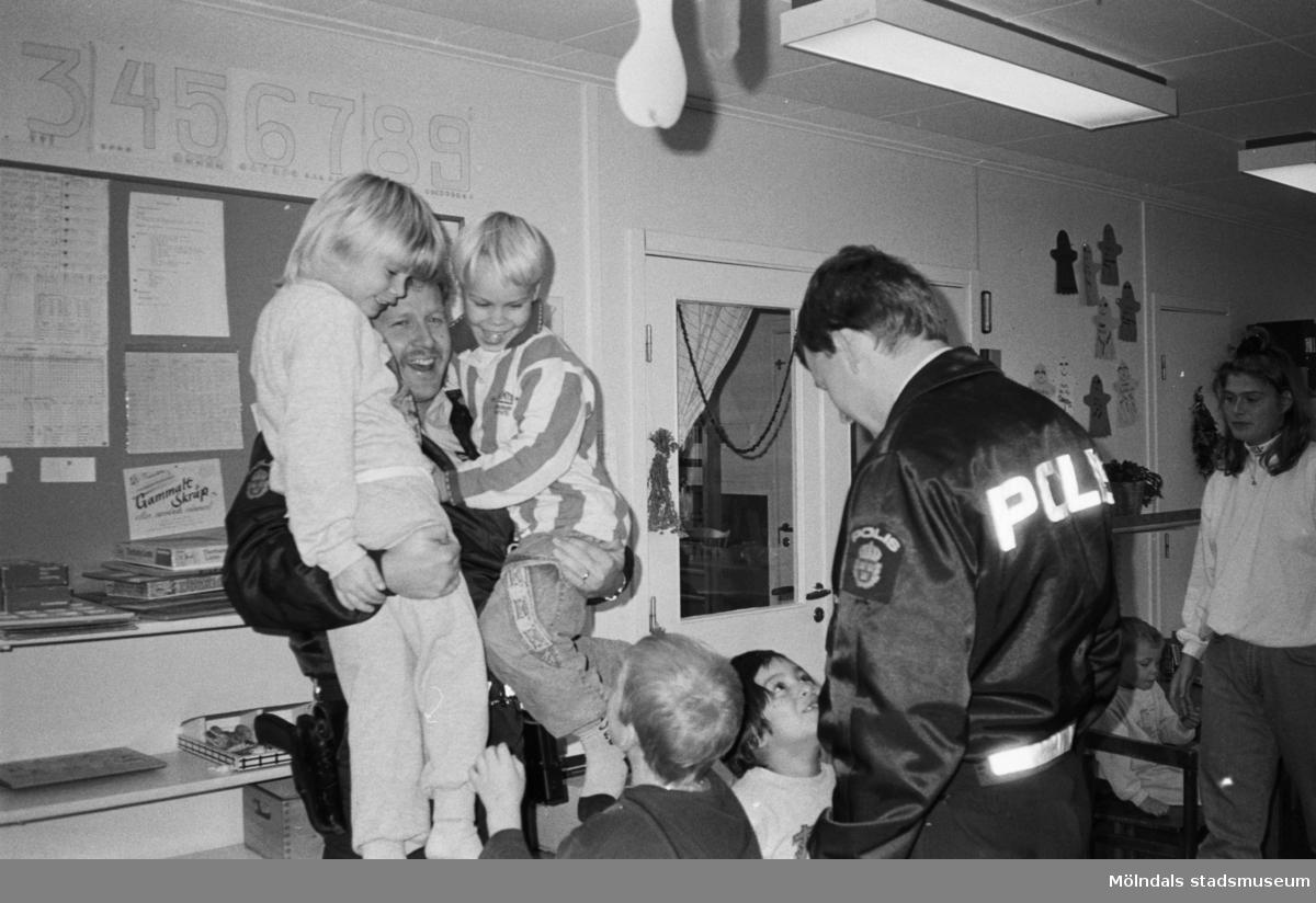 Katrinebergs daghem har besök av två manliga poliser. Dessa är omringade av flera barn varav den ene polisen håller två barn i famnen. Deras fröken står lite vid sidan av. Alla ser mycket glada ut och barnen tittar med stor beundran på männen.