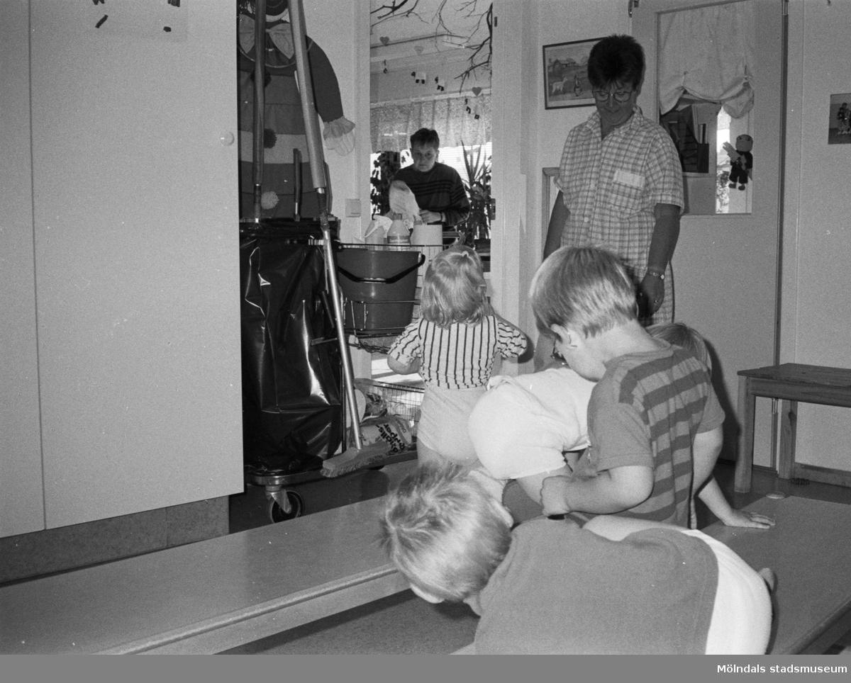 Fyra små barn sitter/står bredvid daghemmets städerska. Ett barn pratar med henne. Vid sidan om står städvagnen. I bakgrunden syns en personal som ordnar i köket. Katrinebergs daghem, 1992.