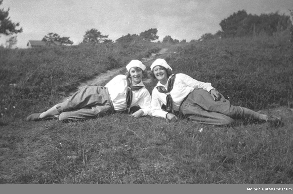 Karin Hasselberg (till höger) och en väninna. Båda ligger i gröngräset iförda fritidskläder, 1940-tal. Relaterat motiv: 1995_0686.