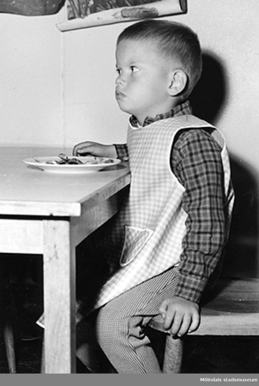 En pojke som sitter och äter. Holtermanska daghemmet 1953.