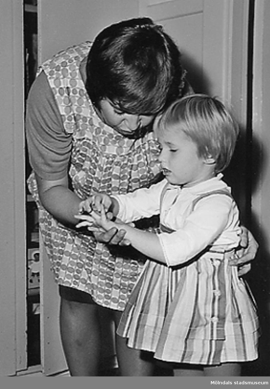En lärarinna som hjälper en liten flicka vid Holtermanska daghemmet 1953.