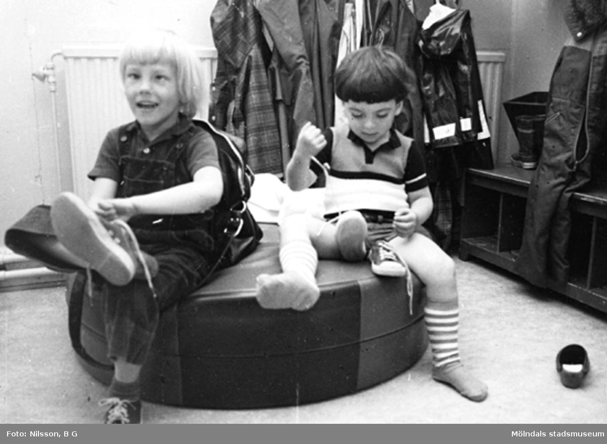 Två pojkar som tar på sig skor. Holtermanska daghemmet, okänt årtal.