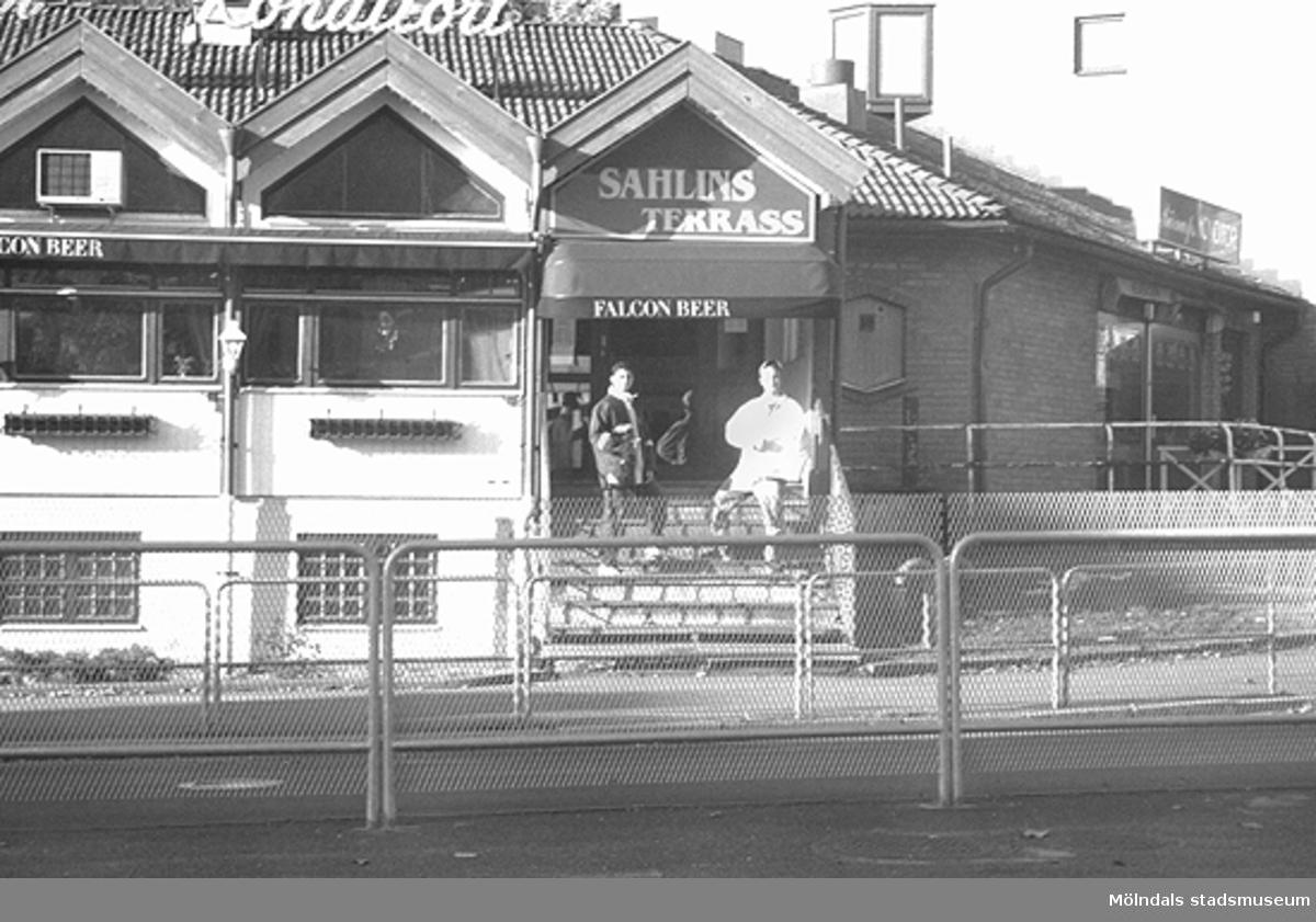 Sahlins Terrass, hörnet Storgatan/Frölundagatan. Mölndalsbro i dag - ett skolpedagogiskt dokumentationsprojekt på Mölndals museum under oktober 1996. 1996_1079-1097 är gjorda av högstadieelever från Kvarnbyskolan 9C, grupp 4. Se även 1996_0913-0940, gruppbilder på klasserna 1996_1382-1405 samt bilder från den färdiga utställningen 1996_1358-1381.