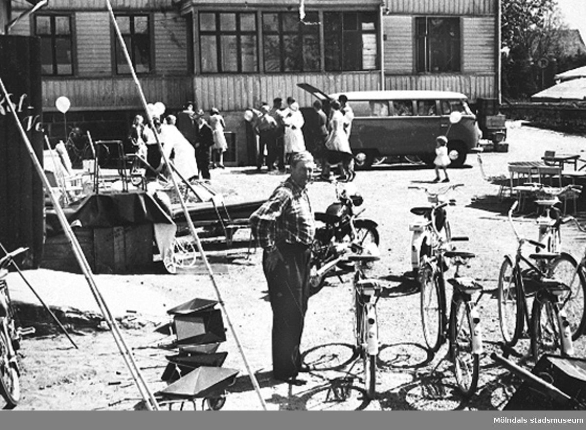 En man står på en gårdsplan bredvid några cyklar. I bakgrunden ses barn och vuxna som packar/packar ur en folkvagnsbuss framför ett stort hus. 1950-1960-tal.
