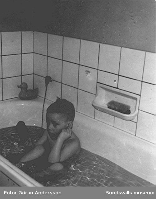 """Håkan Andersson i badkaret i familjens bostad på Sveavägen 33, Sundsvall. Håkan är son till Inge-Britt och Göran Andersson, Sundsvall. Text; """"Tvål i örat Vad är tvålen broder?""""."""