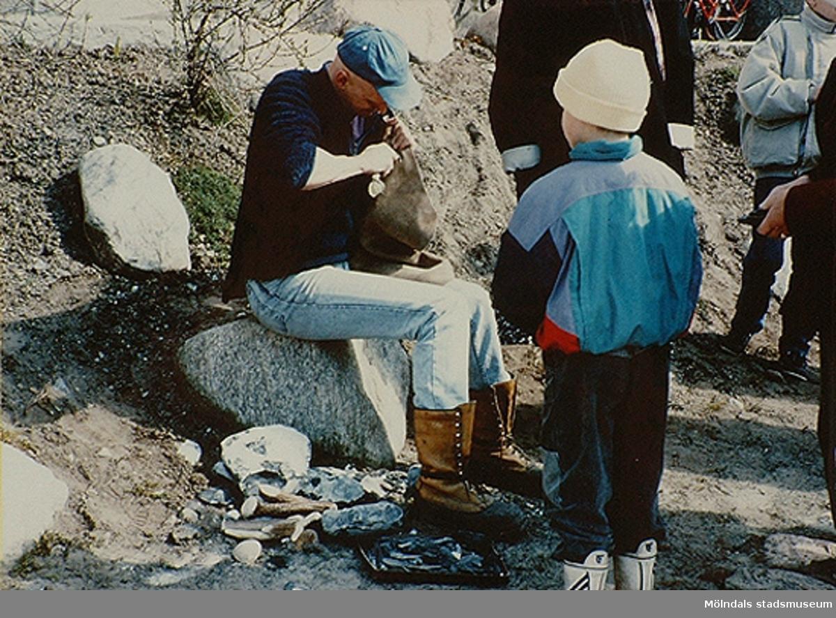 Framför honom står ett litet barn och ser på. Utomhusaktivitet vid museet. Okänt årtal.
