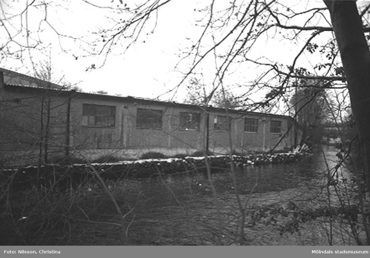 Fabriksbyggnad vid vattendrag.