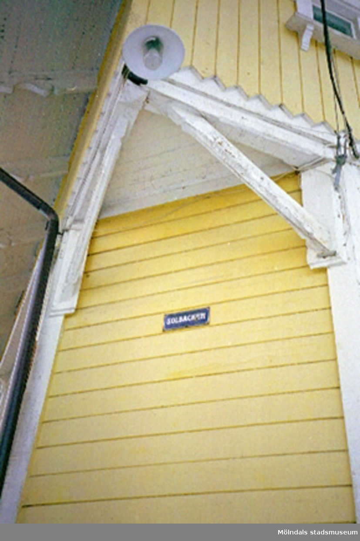 """Ytterfasad med skylt: """"Solbacken"""". Byggnadsdetalj: Lykta."""