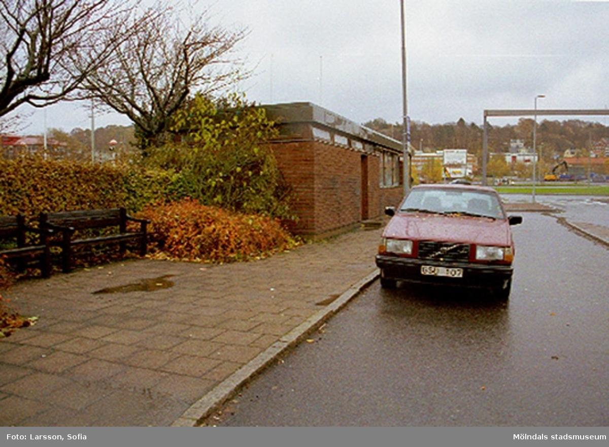 Dokumentation av taxistation. En röd Volvo kombi står parkerad utanför. I bakgrunden går Göteborgsvägen. Okänt årtal. Relaterade motiv: 2002_1172 - 1178.
