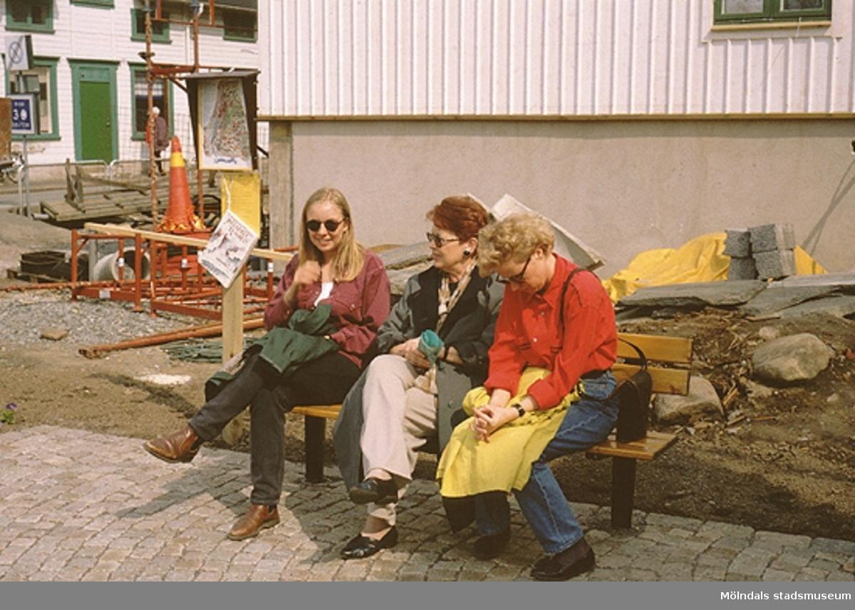 Tre kvinnor sitter på en parksoffa vid Lyktplatsen, Kvarnbydagen 25/4 1993. Gatlyktan (ej i bild) invigs. Kråkans Krog (vitt hus med grön dörr) ses till vänster.