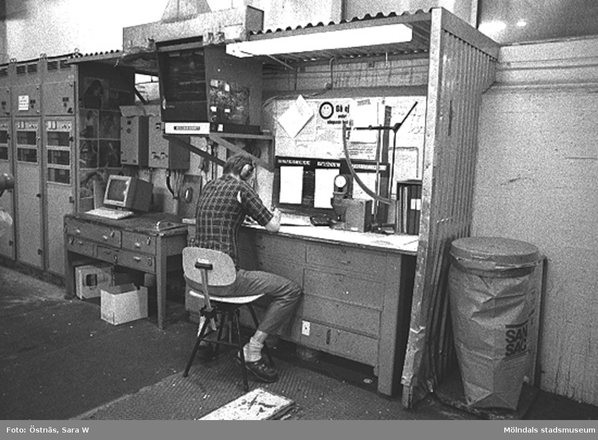 En man i arbete på pappersfabriken. Denny Andersson kontrollerar kartongen, byggnad 6. Bilden ingår i serie från produktion och interiör på pappersindustrin Papyrus.