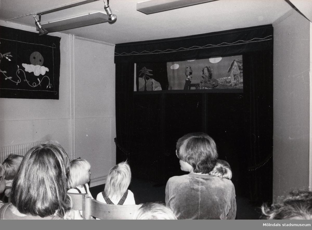 """Föreställning av """"Den förtrollade fisken"""" i TBV:s lokal d. 27/9 1981. Fotografi ur album tillhörande Blanka Kaplan.  Sagan om den förtrollade fisken är en bearbetning Blanka Kaplan gjort av sagan """"Fiskaren och hans hustru"""". Den gick som dockföreställning under året -81 till början av -82 i TBV-husets lokal på Hagåkersgatan 4 i Mölndal.  Den handlar i korthet om en fiskare som en dag får upp en förtrollad flundra på kroken. Fiskarens hustru begär då att fiskaren ska be flundran att förvandla deras fattiga koja till en nätt liten stuga. Flundran uppfyller önskningen, men hustrun vill snart ha mer och mer och blir med tiden både kejsare och påve. Till sist önskar hon sig för mycket."""