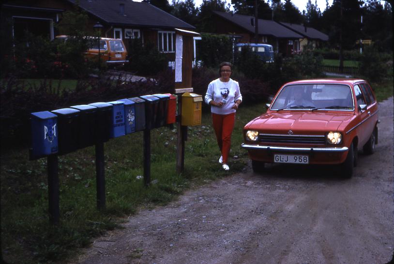 Lantbrevbärare Mikael Mattsson har kommit till Rocksta. Gunvor Wessberg går vid bilen. I förgrunden syns en samling postlådor och en gul brevlåda.