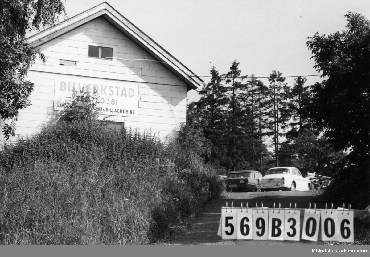 Byggnadsinventering i Lindome 1968. Bräcka 1:12. Hus nr: 569B3006. Benämning: ladugård. Kvalitet: mindre god. Material: trä. Övrigt: vit eternit på synliga gaveln. En bilverkstad. Tillfartsväg: framkomlig.