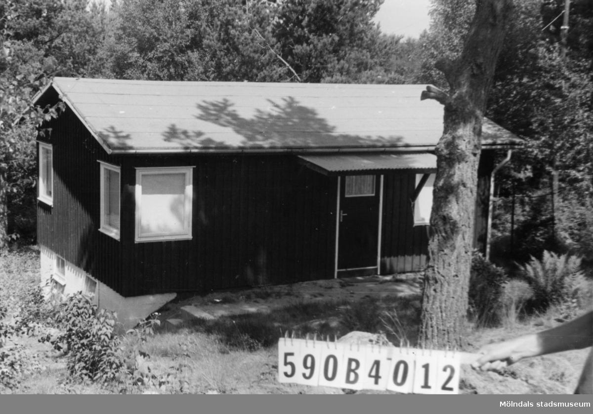 Byggnadsinventering i Lindome 1968. Hällesåker (4:4). Hus nr: 590B4012. Ligger för nära 590B4011 och ska flyttas. Arrenderad tomt. Benämning: fritidshus. Kvalitet: god. Material: trä. Tillfartsväg: ej framkomlig.