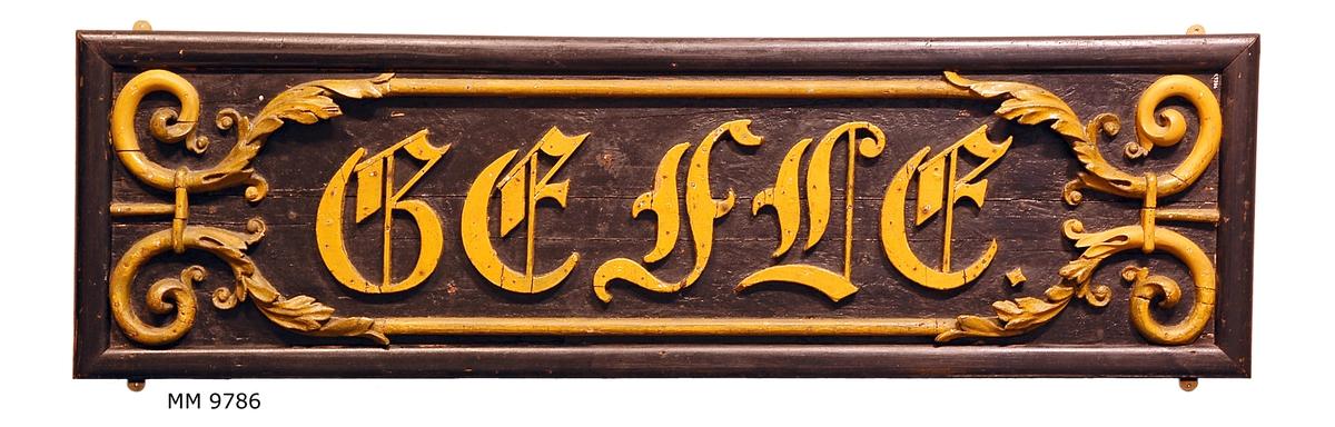 Namnbräda från ångkorvetten Gefle. (Fartyget byggt vid Örlogsvarvet Karlskrona 1847). Försedd med namnet Gefle i skulpterade träbokstäver, omgivna av skulpterad slinga, allt gulmålat. Fäst till svartmålat träplan.