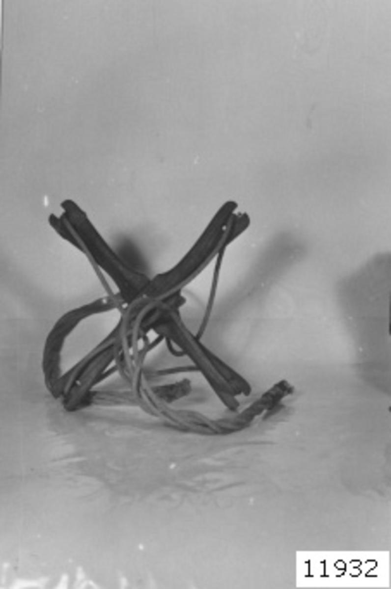Del till logg av ek med linor av bomullsgarn. Består av ett kryss med i mitten ett 10 mm hål. I varje urtag vid kryssets ändar är en lina fastsurrad, och linornas ändar är hopsnodda med varandra på båda sidor om krysset. Ena änden är läderklädd och formad till en ögla, som varit fäst till en varvräknare, den andra till logglinan.