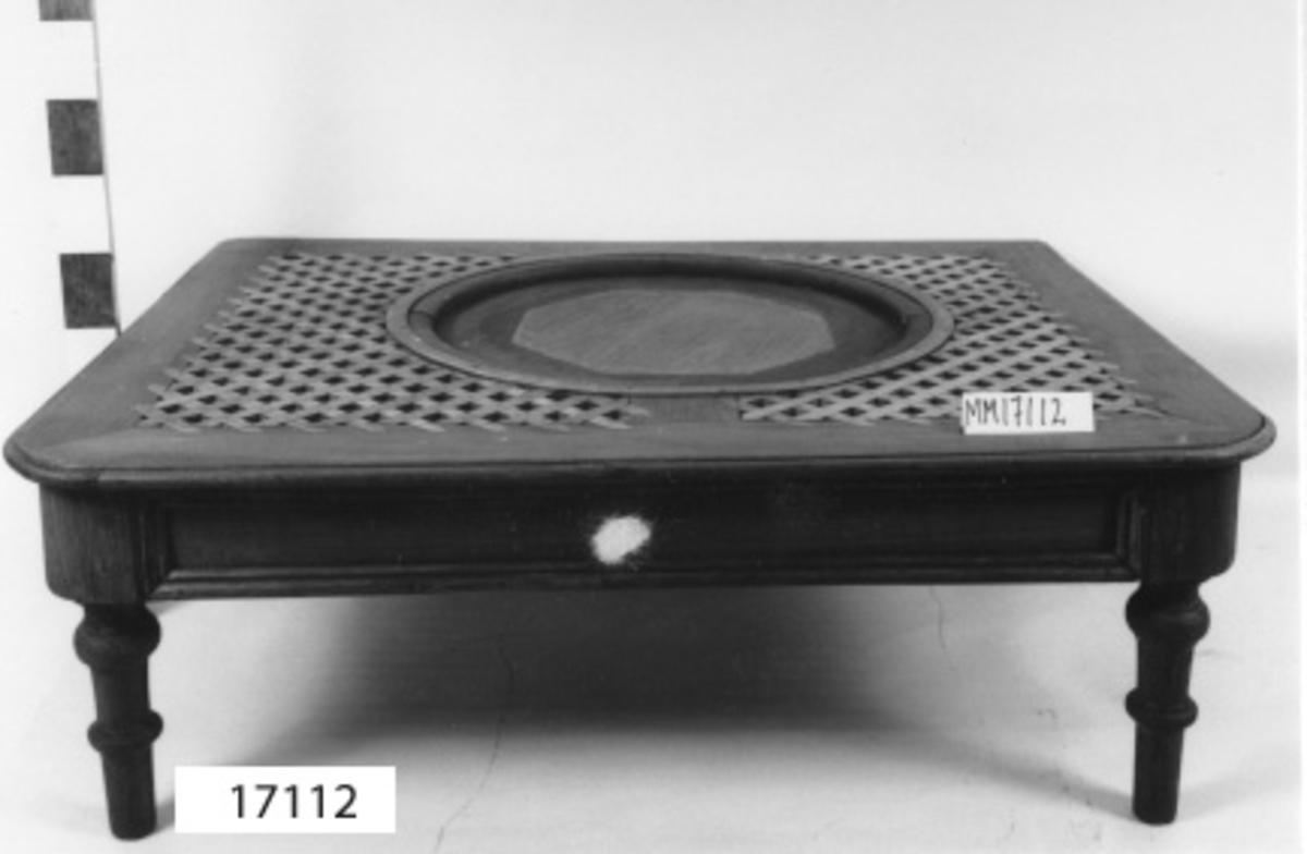 Bord av mahogny med fyra korta svarvade ben fästade i en bred profilerad sarg (115 mm). Ovanpå sargen ligger bordsskivan, som är svängd i ena långsidans hörnor samt profilerad i kanten. Ovansidan utgörs av kant av mahogny (B = 112 mm) och mitten består av korsade, ljusa trälister ( B = 22 mm),lagda så att ett nätmönster bildas. I bordets mitt finns ett hål (D = 959 mm) kantat med trälist samt mässingsband. Sekundär inläggning av plywoodskiva.