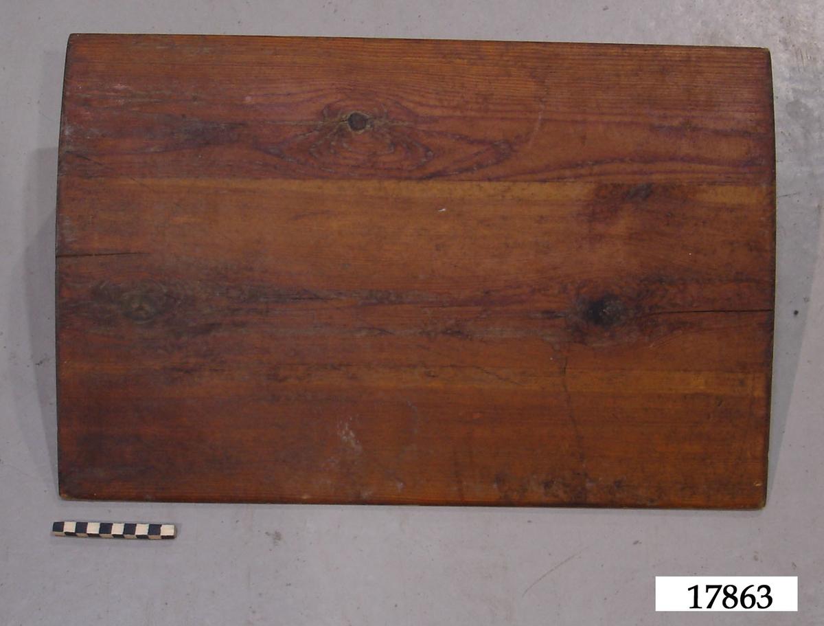 Kudde tillverkad av fur med plan botten, vinkelrät baksida och en ovansida som är svagt konvex och sluttar från baksida till framsida, där den avslutas i en spets. Fernissad på framsidan.
