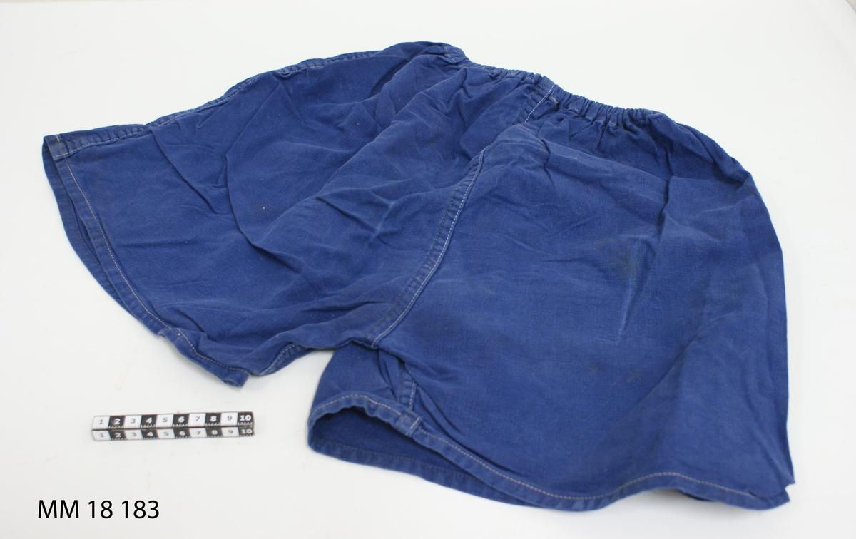Idrottsbyxor av blå bomull, korta ben med resår i midjan. Dubbelstickade sömmar.