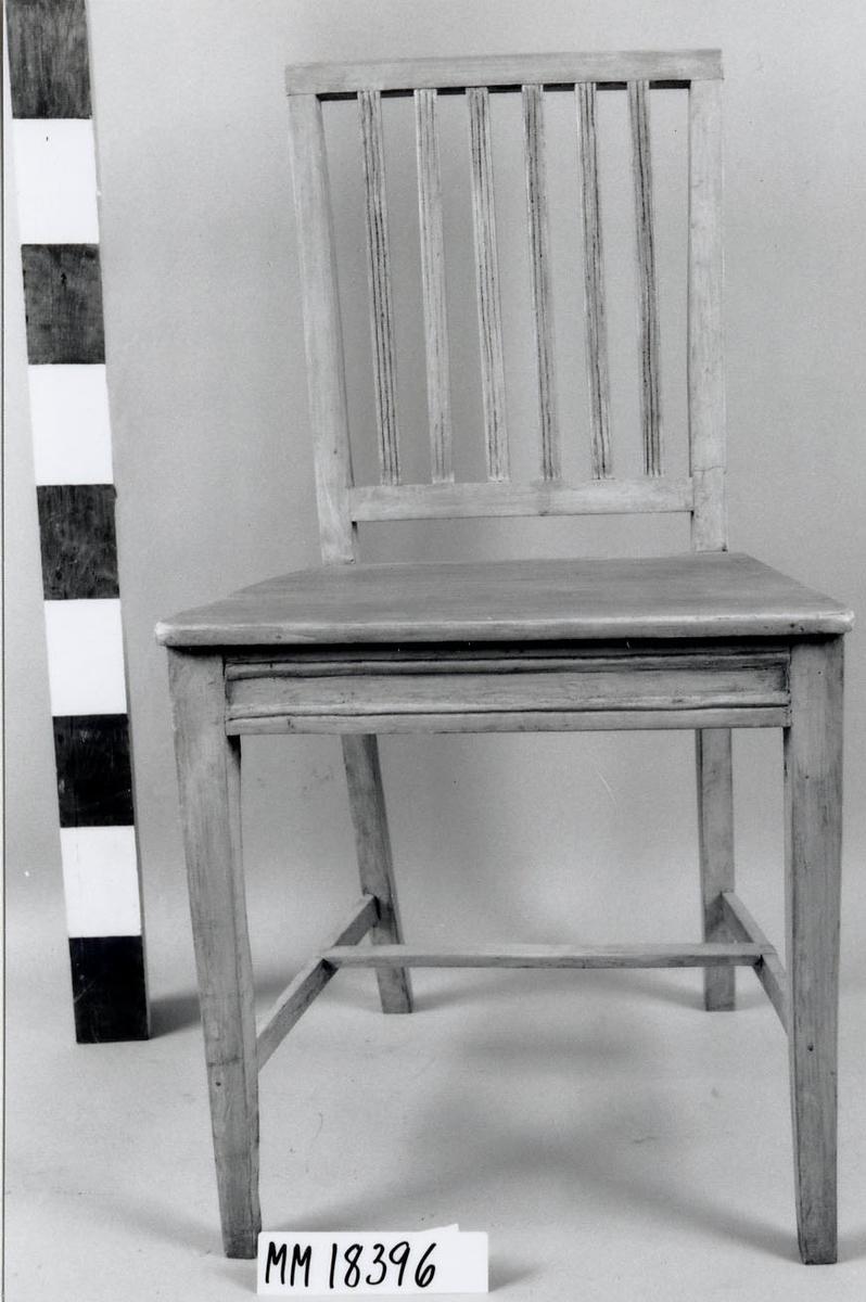 Stol av björk, målad i blekgrön oljefärg. Raka och fyrkantiga ben, bakben svagt böjda och övergår i ryggen. Slåar mellan benen, sk. H-kryss. Rygg med sex spjälor, profilerade med tre smala ränder. Fast sits ovanpå sarg. Samtliga detaljer har fyrkantigt tvärsnitt, delarna är fästade samman med tränit. Sitsens undersida är omålad. Gustaviansk modell.