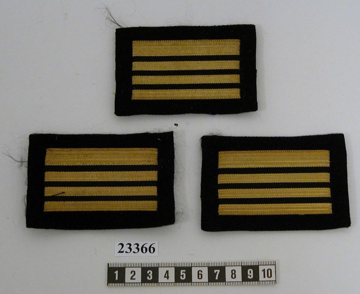 Gradbeteckning (tre stycken) för 1 högbåtsman för ärm. Gradbeteckningen består av en bit svart rektangulärt kläde försedd med fyra streck, varav de tre nedre 6 mm breda, det övre 11 mm brett. Alla streck 70 mm långa.