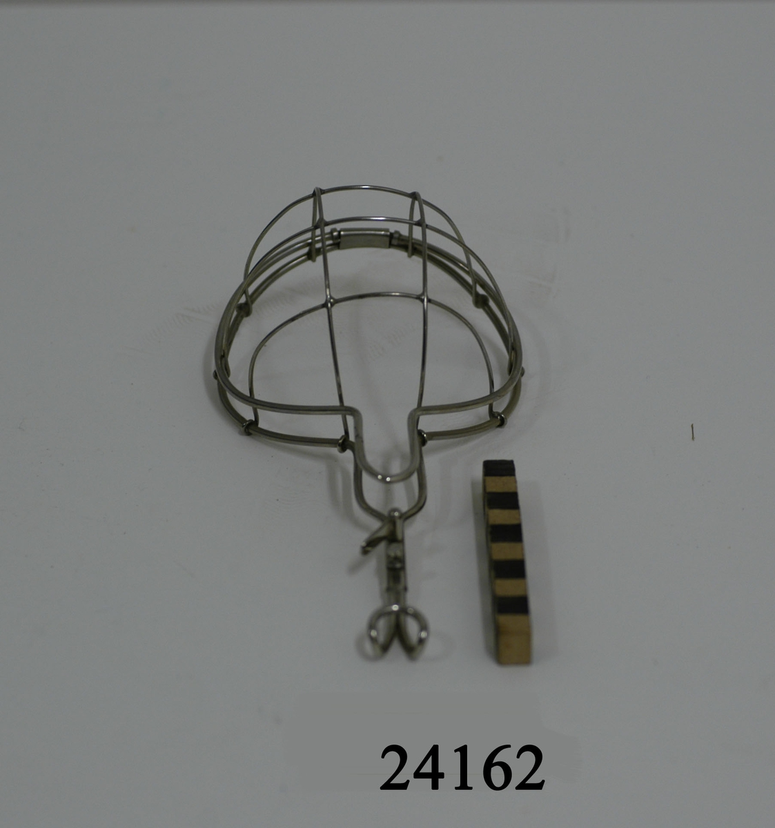 Narkosmask av rostfritt stål, något sväng, gallerförsedd, sex metalltrådar iform av båge. Delen som placeras över näsa och mun är till formen rund.  Dess nedre del är utdragen till en 11 cm smal avlång del och avslutas med handtag uppåtböjd i änden samt låsbar fjäder. I masken övre del ett fäste med bygel som fälls över den gallerförsedda delen och låses i handtaget med fjäder.