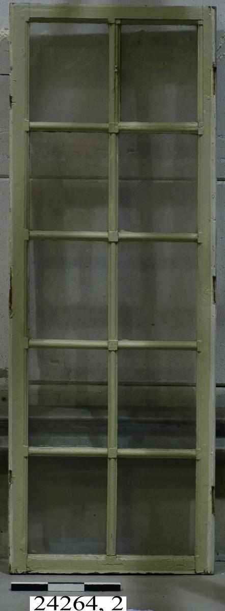 Spröjsat, dubbelt fönster med tolv glas inom ram av trä. Inre glaset ospröjsat. Fönstrets yttre ram grönmålad, den inre vitmålad.
