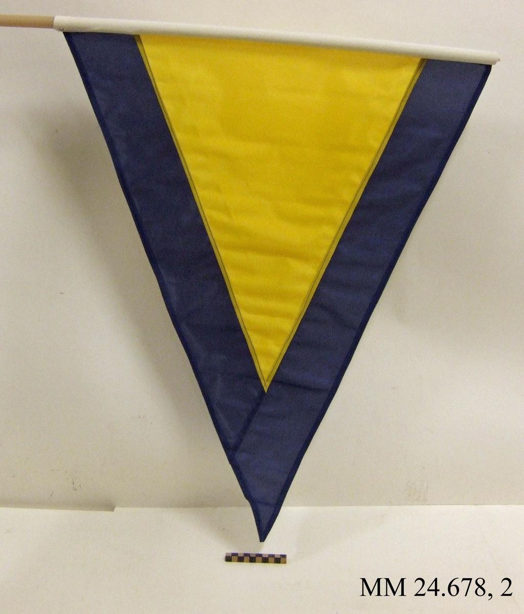 Fartstandert av nylon på rund stång av plast. Även standerten Alfa. Trekantig form, gul med mörkblå kant ca 120mm. Vitt lik trätt på plaststav och skruvat fast. Flaggan ligger i påse tillsammans med tre andra flaggor, sk. fartflaggställ M 8320-034010.