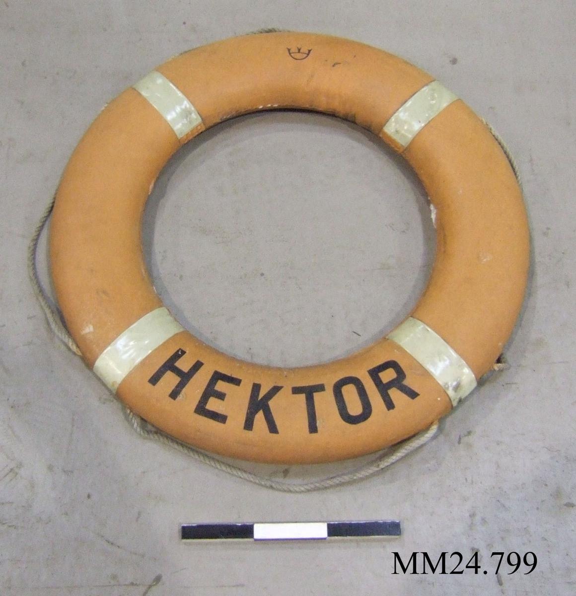 Cirkulär orange frälsarkrans med fyra vita band som fäster det snöre som löper runt kransen. Längst ner på framsidan texten HEKTOR. På baksidan tryck ULVEX Oljebest - Svårantändlig Armerad - Omagnetisk Kungl Sjöfartsstyrelsen 11/388 A/69.