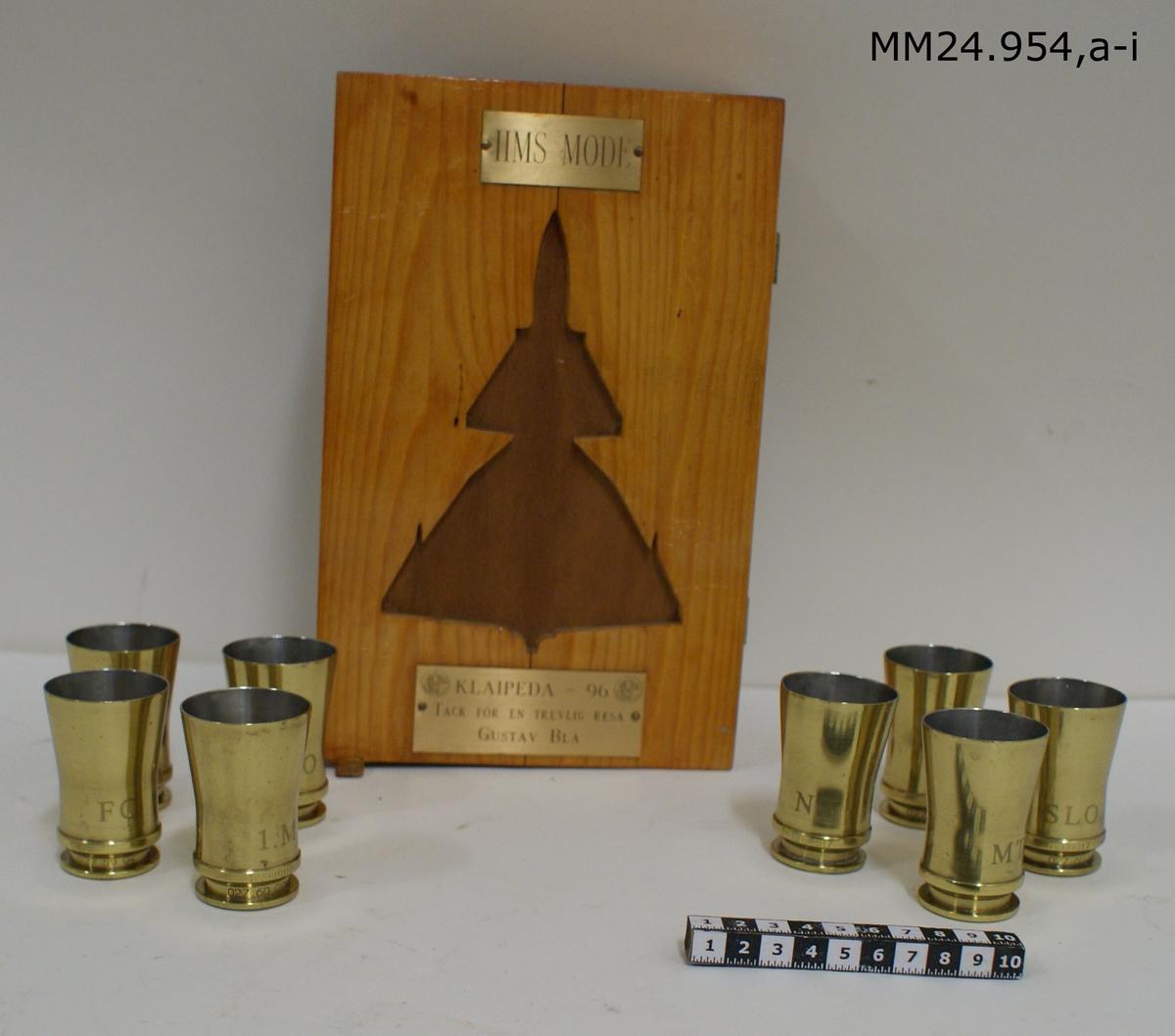 """Åtta stycken snapsglas gjora av avskurna tomhylsor. Snapsglasen märkta efter vilken befattningshavare de tillhör. Följande glas finns: a) FC b) 1.0 c) AO d) MTJC e) 1.M f) NS g) SLO h) PB Förvaras i en trälåda (i). På lådans lock en JA 37 Viggen utskuren. Metallskylt högst upp på locket: """"HMS MODE"""". Metallskylt längst ner på locket: """"KLAIPEDA -96. TACK FÖR EN TREVLIGT RESA. GUSTAV BLÅ"""""""