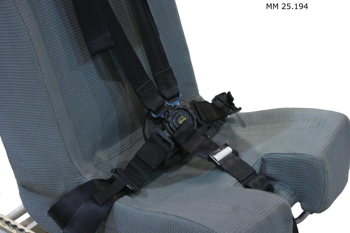 """Stol med vadderad sists och ryggstöd, klädd i grå textil. Nackstöd i grå läderimitation. Stolen försedd med fempunktsbälte i svart textil med plast och metallkoppling. På stolens baksida två framfällbara armstöd. Stolen står på ett mörkgrått stativ i metall som är fäst i ett ljusgrått ytbärgarstativ. På ena långsidan av föremålet sitter två klisterlappar med streckkoder som berättar att stolen har förrådsbenämning """"Operatörsstol"""" och förrådsbeteckning M7207-150010 samt att den undre delen har förrådsbetckning """"Ytbärgarstativ"""" och förrådsbeteckning F1472-00707. Stolens individnummer är 666."""