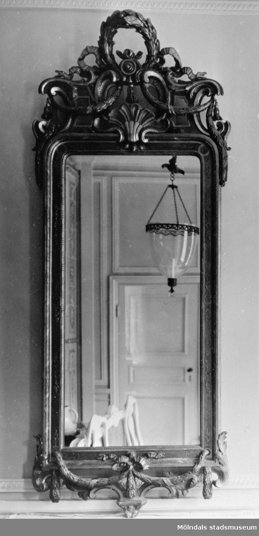 Vägghängd avlång spegel med dekor. I spegelglaset ses delar av ett rum med enkeldörr och taklampa. Gunnebo slott 1930-tal.
