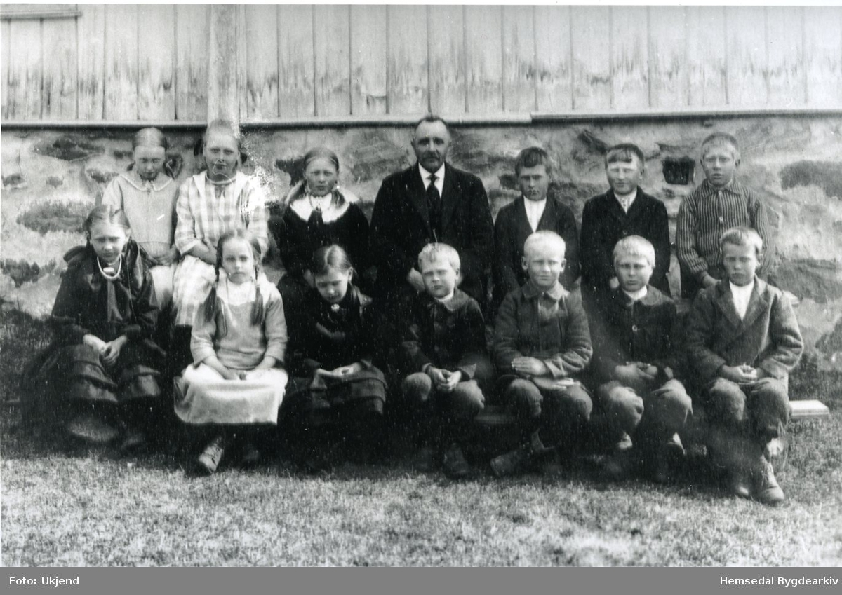 Skulen i Grøndaleni Hemsdal 1923-1924 Fyrste rekke frå venstre: Barbro Fekene, fødd 1915, gift Grøndalen; Anne Rustehaugen; Kari Fekene (Træet);  Olaf Grøndalen Grohaug, fødd 1915; Marius Bredesen,   pleieson i Vente; Knuat Rustehaugen.    Andre rekke frå venstre: Liv Dokken, fødd 1915; Anne Hjelmen, fødd 1915, gift Groset; Anne Grøndalen (sørpågarden), fødd 1915; lærar Otto Sletten;  Ola Rustehagen; Halvor Grøndalen (sørpågarden), fødd 1911; Oskar Hjelmen, fødd 1913.