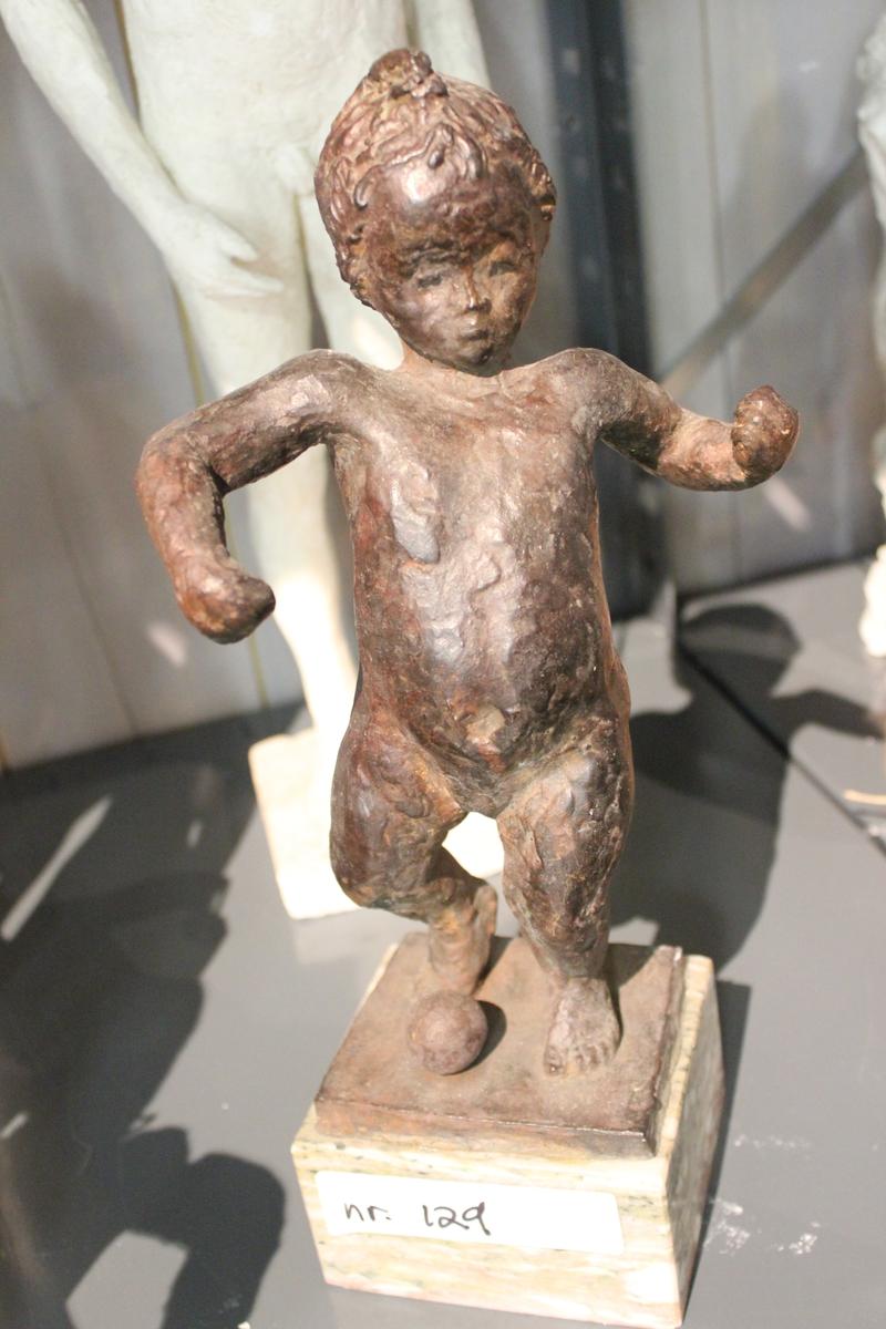 """Skulptur i bronse av et barn på sokkel av marmor. Tittel: """"GUTT MED BALL"""". Se også nr.107, nr.108, nr.127 og nr.128."""