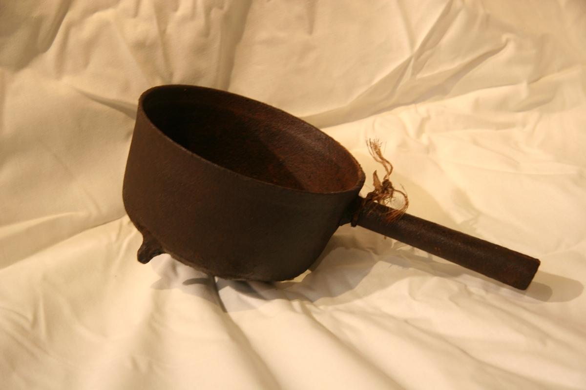 Skaftegryte i jern, gryteforma. 3 bein, det eine nesten borte. Rusta hol i botnen.
