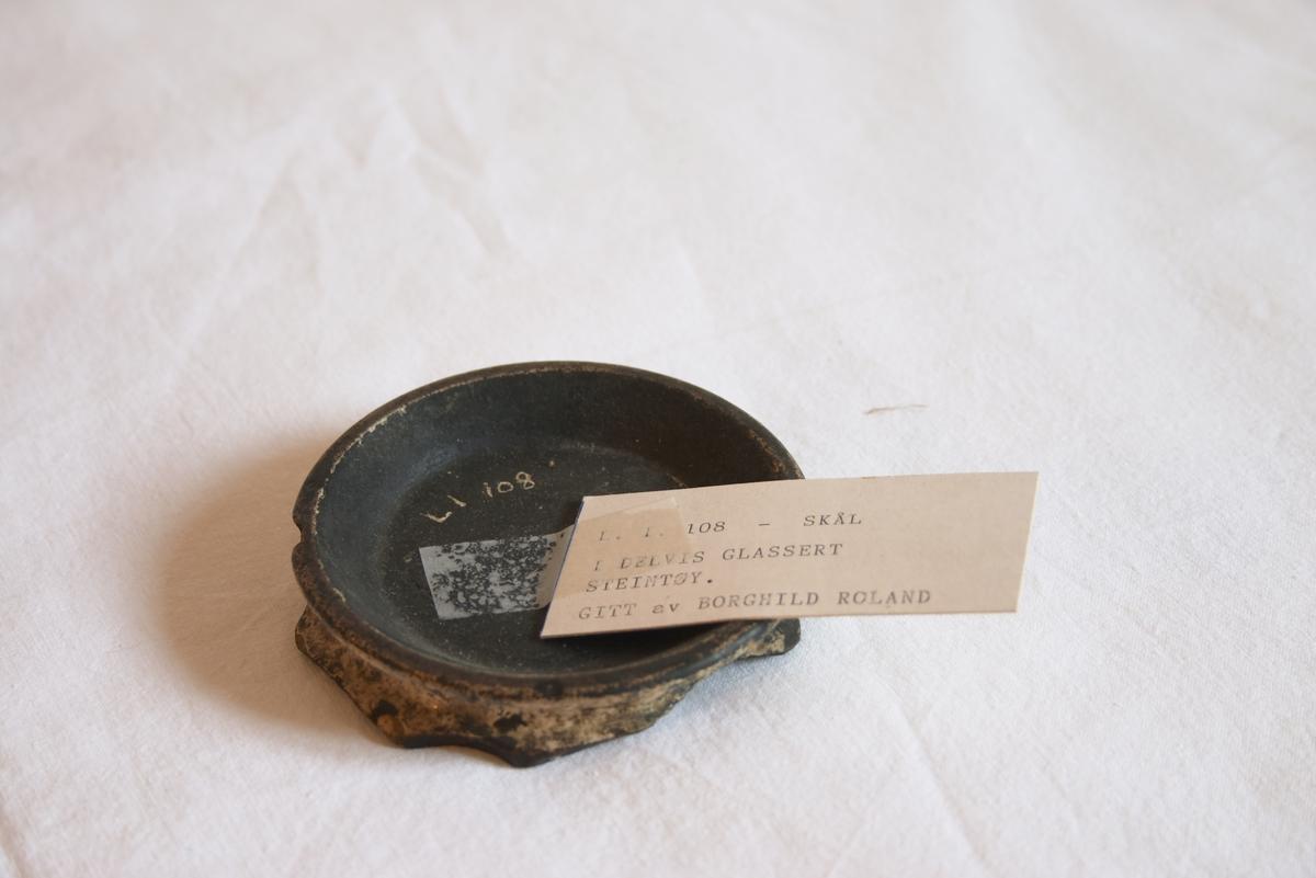 Skål. Delvis glasert steintøy. Svart inni. Sirkelformet med lav skråkant. Underkanten er svært ujevn og bulkete.